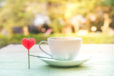 A red heart shaped candle with a cup of coffee and a coffee spoon on a saucer placed on a wooden table in the garden. Valentine day and love concept.