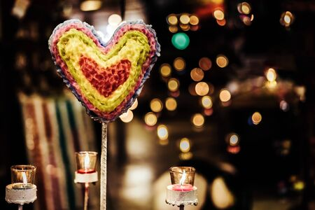 Heart shaped candle and candlelight from small glass cups with bokeh in the background. A valentine's day background. Stock fotó