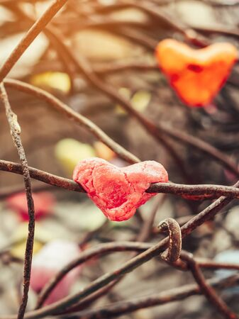 A chunk of a red heart shaped candle adheres to an old rusted steel rod.  A valentine's day background. Stock fotó