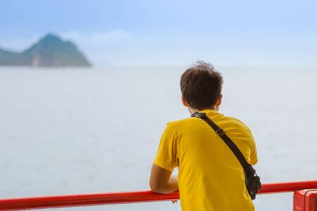 Asian man stands on baluster of ferry for relaxing and look at the ocean and island. 免版税图像