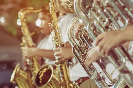 Male student with friends blow the euphonium with the band for performance on stage at night. Stock fotó