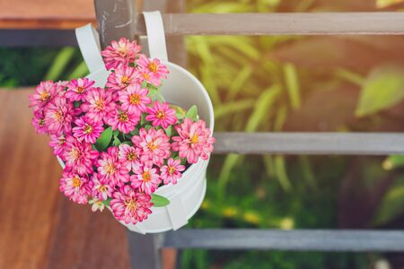 Beautiful artificial flowers in small pots hanging to decorate a railing walk for beauty on the pathway in public gardens. Selective focus.