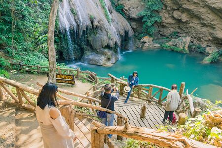 LAMPHUN THAILAND - DECEMBER 9 :  Unidentified female tourists taking pictures and selfies on December 9, 2019 at Ko-luang waterfall in Lamphun, Thailand.