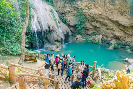 LAMPHUN THAILAND - DECEMBER 9 :  Unidentified female tourists taking pictures and selfies on December 9,2019 at Ko-luang waterfall in Lamphun, Thailand.