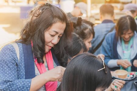 LAMPHUN THAILAND - DECEMBER 12 :  Unidentified Thai female tourists learn to make a necklace from a yarn ball on December 12,2019 at Karen village in Lamphun, Thailand