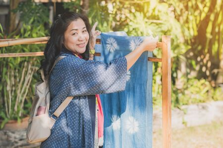 LAMPHUN THAILAND - DECEMBER 12 :  Unidentified Thai female tourists learn to make tie-dye clothes on December 12, 2019 at Karen village in Lamphun, Thailand 新聞圖片