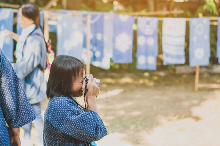 LAMPHUN THAILAND - DECEMBER 12 :  Unidentified Thai female tourist take a photography while her friends learn to make tie-dye clothes on December 12, 2019 at Karen village in Lamphun, Thailand