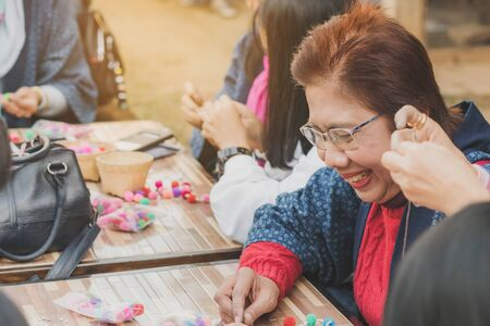 LAMPHUN THAILAND - DECEMBER 12 :  Unidentified Thai female tourists learn to make a necklace from a yarn ball on December 12, 2019 at Karen village in Lamphun, Thailand