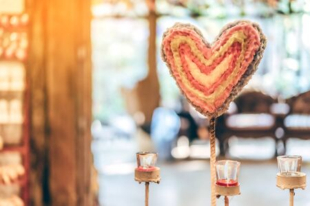 Heart shaped candle and candlelight from small glass cups. A valentine's day background. Stock fotó
