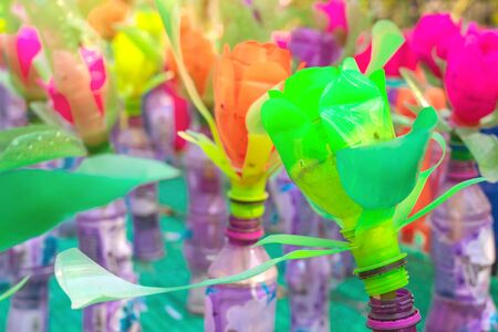 Recycled colorful plastic flowers made from plastic bottles to decorate as flowers in the garden. Plastic bottle recycled.