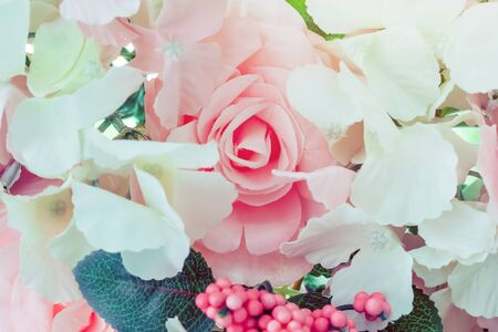Many artificial pink and white roses are decorated on the glass door to the backdrop in the afternoon. Beautiful flowers background, Selective focus.