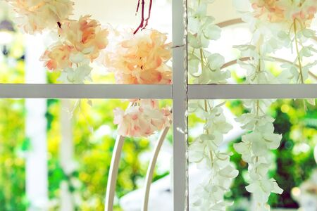 Beautiful artificial flowers hung on glass windows to decorate for a garden party. View from the window on the glass.