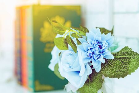 Beautiful artificial blue roses in glass vase on a white table with blured image of three books in the background.