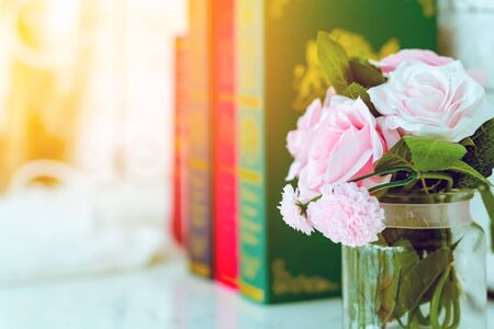 Beautiful artificial pink roses in glass vase on a white table with blured image of three books in the background.