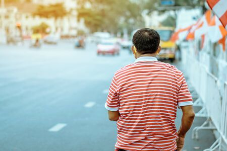 Back view of male patient with mask in red and white shirt standing at bus stop and wait for taxi or bus in the city to go to the hospital.