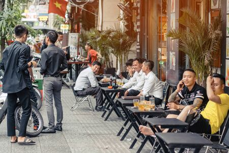 HO CHI MINH CITY, VIETNAM - APRIL 24, 2019 : Unidentified people drink coffee, tea or juice fruit on cafe stall on sidewalk on april 24,2019 in Ho Chi Minh City, Vietnam.  Drinking on street is a typical culture of Vietnamese.