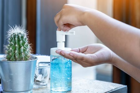 Young woman uses her hand to press hand sanitizer bottle to clean her hand. Hand sanitizer alcohol gel rub clean hands hygiene prevention of coronavirus virus outbreak. Concepts of Flu virus, Covid-19 (Coronavirus disease).
