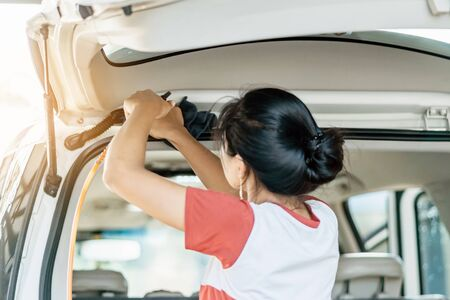 Woman cleaning with a blowers and microfiber wipe the car polishing after car wash. Selective focus on left hand.
