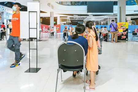 KANCHANABURI/ THAILAND - APRIL 4 2020: Unidentified people order food to take home inside of Robinson closes due to the corona virus (Covid-19) outbreak but opens only food section at Robinson Department Store. Restaurants set chairs for waiting for the f Reklamní fotografie - 144091075