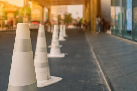 The white traffic cones are set up as a pedestrian safety zone in front of the mall. Stockfoto