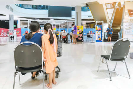 KANCHANABURI/ THAILAND - APRIL 4 2020: Unidentified people order food to take home inside of Robinson closes due to the corona virus (Covid-19) outbreak but opens only food section at Robinson Department Store. Restaurants set chairs for waiting for the f