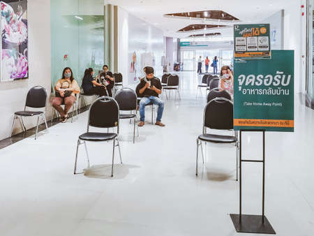 KANCHANABURI/ THAILAND - APRIL 6,2020: Unidentified people order food to take home inside of Robinson closes due to the corona virus (Covid-19) outbreak but opens only food section at Robinson Department Store. Restaurants set chairs for waiting for the f Redakční