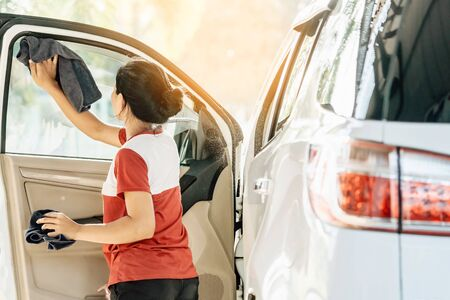 Woman cleaning with a blowers and microfiber wipe the car polishing after car wash.