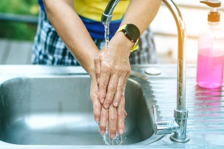 A woman washing hands from the tap with pink soap in a aluminium tub. Concepts of Flu virus, Covid-19 (Coronavirus disease). Selective focus.