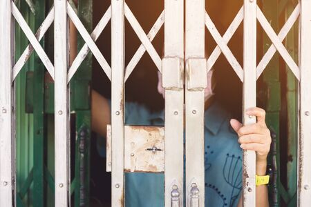 A woman wear surgical face mask and home quarantine herself in house by holding steel door stretch and look at the out side. Social distancing for protect Covid-19 concept.Selective focus on left hand