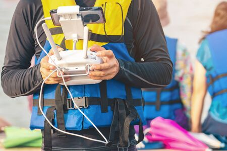 Young man in blue and yellow life vest controlling a drone to take pictures of ocean coast with tourists while traveling on a raft in the sea. Hands holding drone remote controller.