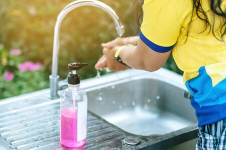 A woman washing hands from the tap with pink soap in a aluminium tub. Concepts of Flu virus, Covid-19 (Coronavirus disease). Selective focus on soap bottle.