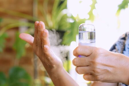 Woman using alcohol nano mist sprayer antiseptic cleaning on her hands protection during Coronavirus pandemic Covid-19.Hand using sanitizer spray.Modern health technology concept.New normal lifestyle.