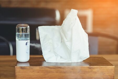 Alcohol nano mist sprayer for hand cleaning to prevent the spread of the corona virus (Covid-19) placed on the table to serve customers before buying in the coffee shop. Modern health technology. Фото со стока