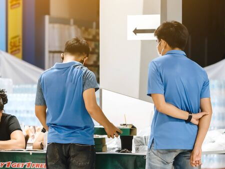 Back view of men order pizza to take home inside of department store closed due to the corona virus (Covid-19) outbreak but opens only food section