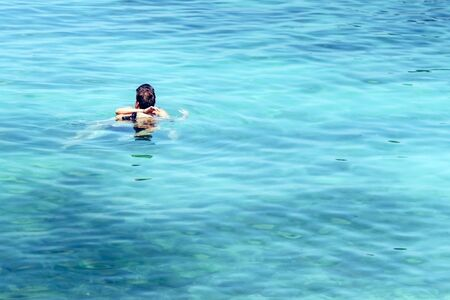 Young strong man in love hugging and embracing girlgriend in a bikini suit in the sea. Beautiful couple in the sea.