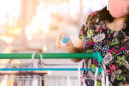 Woman wear mask using alcohol nano mist sprayer antiseptic cleaning on shopping cart trolley handle protection during Coronavirus pandemic Covid-19. Wipe clean the surfaces with disinfectant.