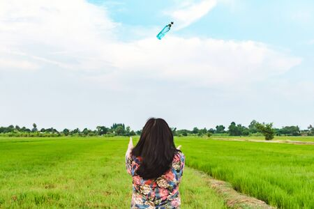 Back view of woman raises her arms to wait for alcohol gel bottle falling from the sky in the rice field.Campaign to prevent the spread of the Corona virus(Covid-19).New normal concept.Selective focus