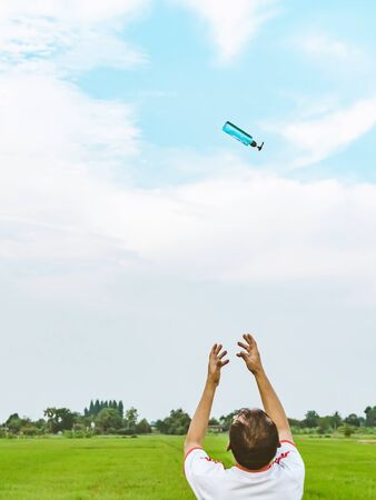 Back view of man raises his arms to wait for alcohol gel bottle falling from the sky in the rice field.Campaign to prevent the spread of the Corona virus(Covid-19).New normal concept.Selective focus Banco de Imagens