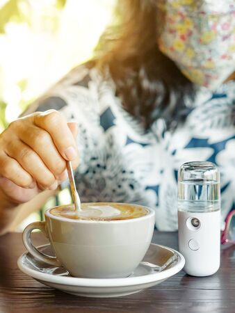 A quarantined woman relax with hot cappuccino coffee and alcohol nano mist sprayer on table while being quarantined due to the Corona virus (Covid-19) outbreak. New normal concept. Selective focus 免版税图像