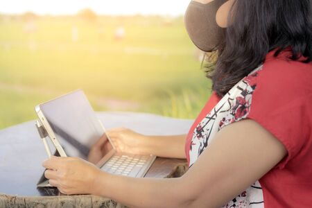 A quarantine woman wear a protective mask to prevent the spread of of the Corona virus (Covid-19) ,Use a laptop to work from home in the rice field. New normal concept.Selective focus