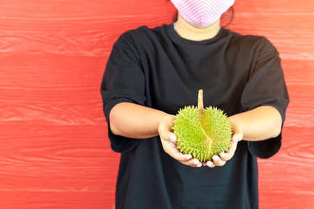 Young woman wear a protective mask to prevent infection of corona virus (Covid-19) in a black shirt holding a ripe durian, ready to eat with the red wooden wall. New normal life style concept.