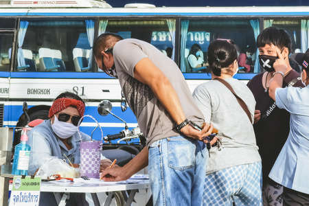 KANCHANABURI,THAILAND-JUNE 28,2020:Examination of body temperature and register identity using QR code or registration book before entry to prevent the spread of Coronavirus(Covid-19)at Local market 新闻类图片