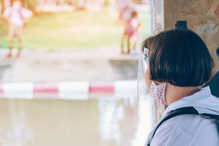 Female elementary school student wear face mask to prevent the Coronavirus(Covid-19) wait for her parents to pick her up to return home after school and the rain just stop in front of the school gate