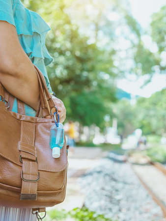 Mini portable alcohol gel bottle to kill Corona Virus(Covid-19) hang on a leather shoulder bag of a woman wearing a mask to shopping in supermarket.New normal lifestyle.Selective focus on alcohol gel Stockfoto