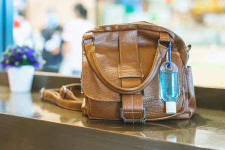 Mini portable alcohol gel bottle to kill Corona Virus(Covid-19) hang on a brown leather shoulder bag on table in coffee shop.New normal lifestyle. Health care concept. Selective focus on alcohol gel Banco de Imagens