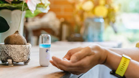 Alcohol nano mist sprayer for hand cleaning to prevent the spread of the Corona virus (Covid-19) to serve customers at coffee shop. Modern health technology. New normal lifestyle. Selective focus