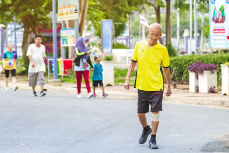 KANCHANABURI, THAILAND-AUGUST 20,2020 : Unidentified Asian elderly man in fitness wear walking and jogging for good health at public park in Tha Muang district Kanchanaburi ,Thailand.