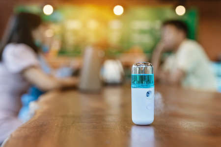 Alcohol nano mist sprayer for hand cleaning to prevent the spread of the virus to serve customers at coffee shop. Modern health technology. New normal lifestyle. Selective focus Foto de archivo