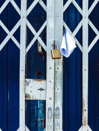 White paper notification attached to closed retractable folding metallic gate.Metal collapsible sliding grille door normally use at shop houses in Asia. Bulletin sticking out at the gate of the house.
