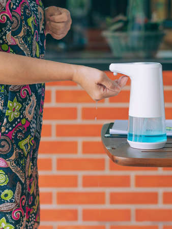 Automatic alcohol dispenser for cleaning hand to prevent the spreading of virus on table before entrance to cafeteria. Healthcare concept. New normal lifestyle. Selective focus 免版税图像